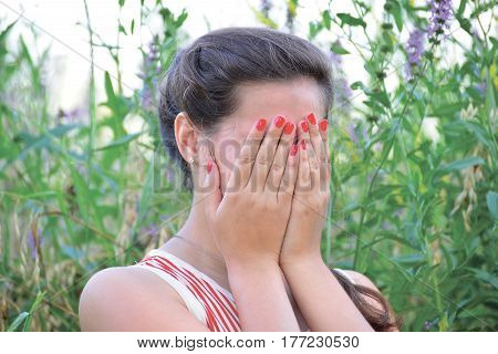 Upset woman covers her face with hands
