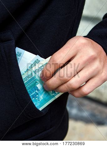 Person hold the Russian Currency in the Pocket on the Street closeup