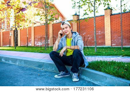 Cheerful Teenager with Cellphone sit on the City Street