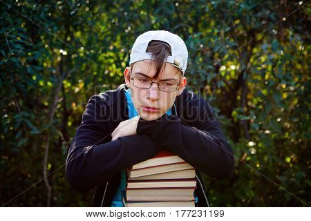 Sad Teenager with a Books on the Nature Background
