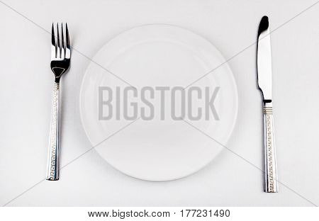 Empty Plate with a Cutlery on the White Table