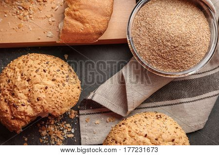 Glass bowl of bread crumbs and broken loafs on grey background