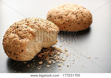Broken buns with sesame seeds on grey background