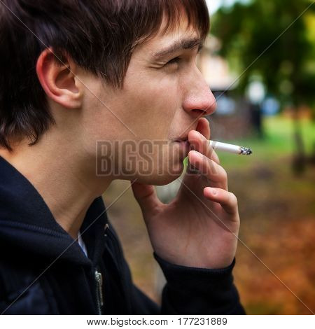 Young Man smoking cigarette in the Park