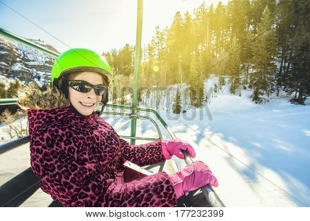 Young skier riding the chair lift on a beautiful ski day