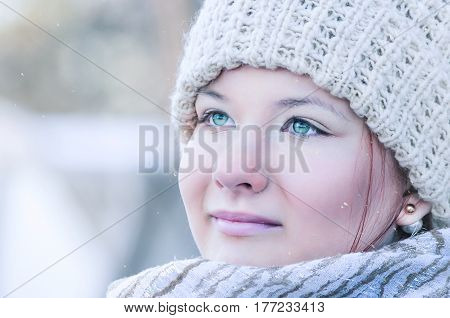 Close-up portrait of a young woman´s face with beautiful green eyes wearing a beige knitted hat and natural make-up is gazing in the distance at the falling snow.