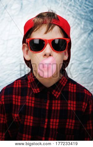 Funky young boy wearing red sunglasses, red baseball cap and a red checked shirt is blowing pink bubbles with his bubble gum on silver background.