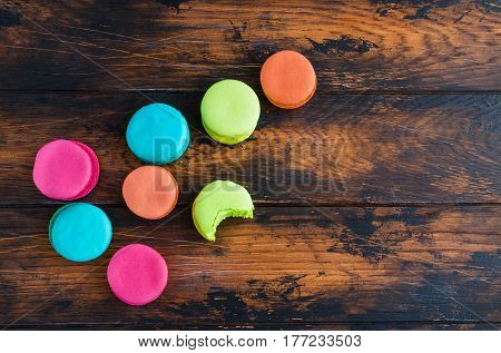 Colourful macaroons or macarons pink blue green and orange whole and bitten ones lying randomly on the dark wooden rustic table top view.
