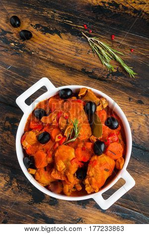 Chicken Cacciatore braised with wine and tomatoes traditional Italian dish. White casserole on the wooden rustic table top view.
