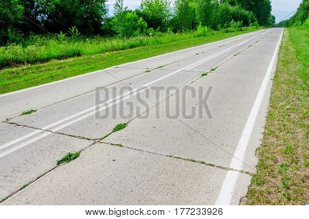 An old concrete road with grass coming through it