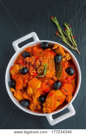 Traditional Italian dish Cacciatore chicken braised with wine and tomatoes. White casserole and a rosemary on the black stone background top view.