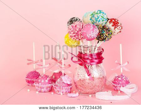 Cake Pops With Pink Icing And Decoration On Paper Form And Colorful Cake Pops In Glass Vase