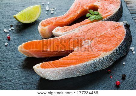 Two big raw salmon steaks fresh lime salt and pepper on a black stone board.