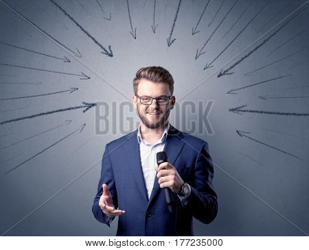 Businessman speaking into microphone with arrows pointing towards his head