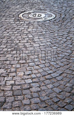 Cobble walkway with sewer cover as background