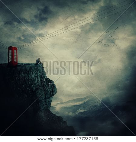 Surreal view as a sad young man standing on the edge of a cliff near a red telephone box waiting someone to call him.