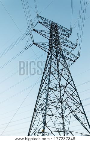 High voltage tower against blue sky. Low angle view