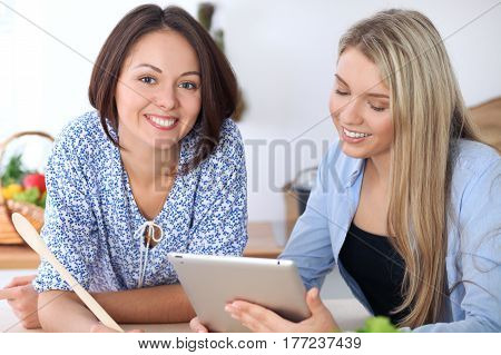 Two young happy women are making online shopping by tablet computer and credit card. Friends are going to cook in the kitchen, they searching internet for a new recipe