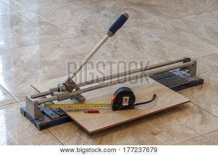 Ceramic tiles and tools for tiler. Floor tiles installation. Home improvement renovation - ceramic tile cutting tool.