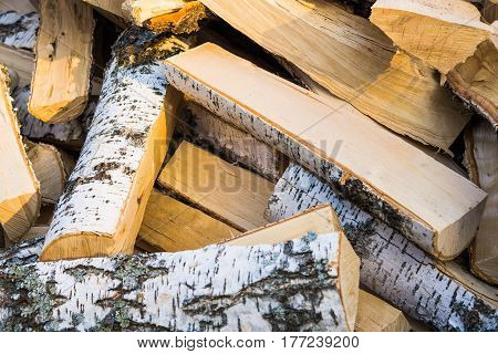 Birch firewood close-up in a chaotic manner