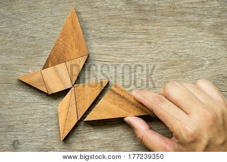 Man hold triangle to fulfill tangram puzzle in butterfly shape (Concept for freedom free life or explore new world)