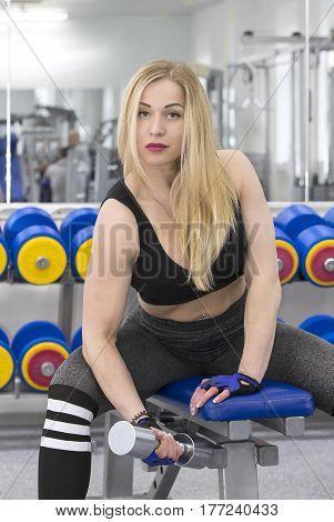 Young girl is engaged in power fitness in the gym