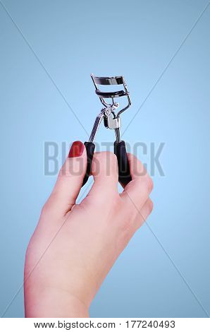 Woman´s hand holding silver metal eyelash curler.