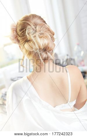 Professional bridal knot of hair. Blonde bride photographed from behind.