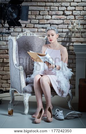 Attractive young actress in retro style reading script, looking at camera.