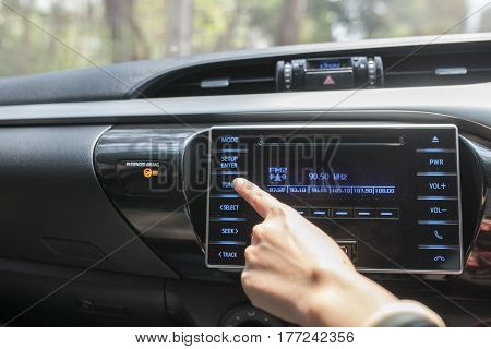 Close up driver hand adjust audio button in the car