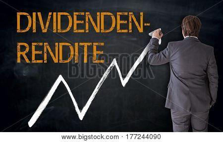 Businessman Writes Dividendenrendite (in German Dividend) On Blackboard Concept