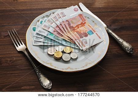 Russian rubles - thousands and five thousands bank notes and different coins on a vintage plate with old silverware