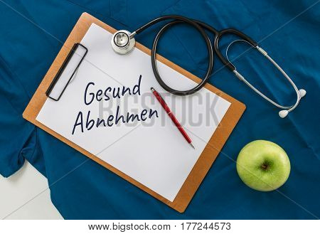 Gesund Abnehmen (in german Healthy Dieting) Clipboard with stethoscope.