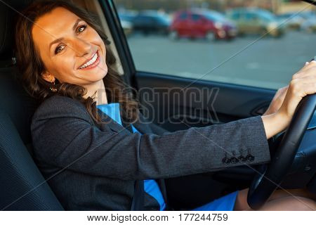 Beautiful woman sits in a car in a parking near a shopping center