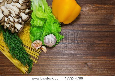 Pasta salad leaves bell pepper mushrooms and garlic shooted on oldened wooden table as a background