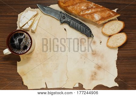 Old paper sheets on the wooden table with baguette bread cup of coffee camembert or brie cheese and a jackknife