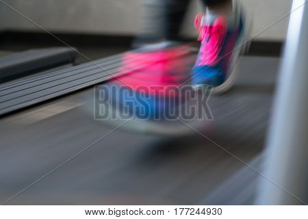 Woman running on treadmill in gym, blured