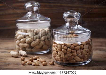 Fried peanuts and peanuts in a peel in glass jars
