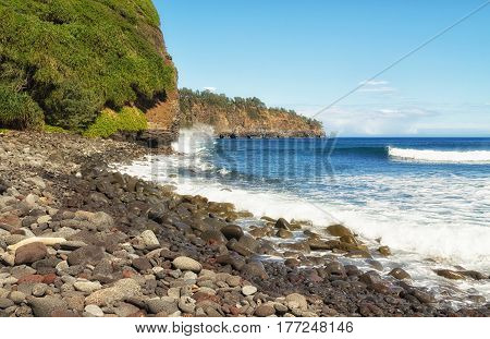 Surf crashes into rocky shore and cliffs of Kohala eroding cliffs. Cliffs along the north coast of the Big Island of Hawaii the Pacific ocean and blue sky with light clouds on a sunny day. View from Pololu Valley beach in February.