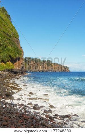 Portrait orientation of rocky Hawaiian beach on a sunny day from the rocky beach of Pololu Valley.