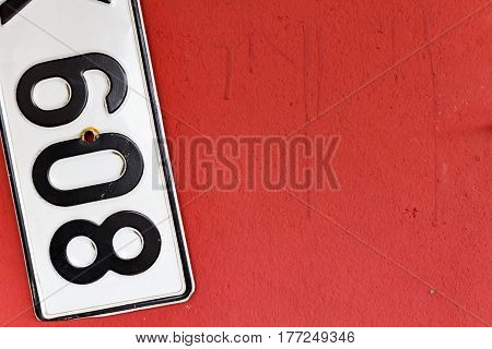 Fragment of car registration numbers hanging on the wall. Abstract background