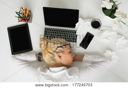Woman sleeping on the office table with gadgets