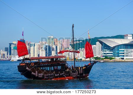 Red sail Chinese wooden junk boat sailing in Victoria habour Hong Kong