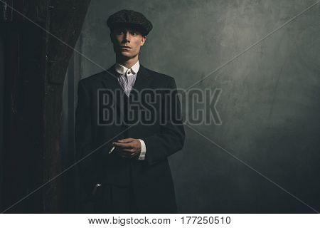 Retro 1920S English Gangster Standing With Cigarette. Wearing Suit And Flat Cap.