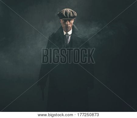 Threatening Retro 1920S English Gangster Holding Gun In Smoky Room.