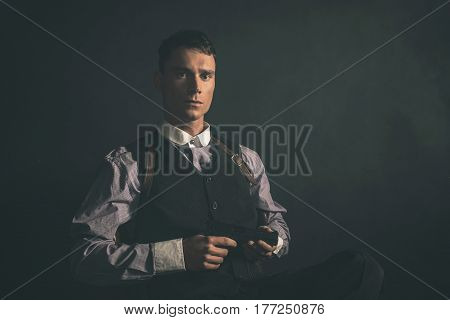 Threatening Retro 1920S English Gangster Sitting With Gun.