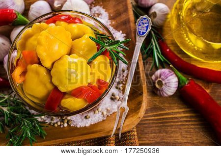 Marinated yellow pattypan and paprika on a wooden background. Selective focus.