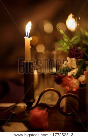 Wedding decor with burning candles on a table in darkness.
