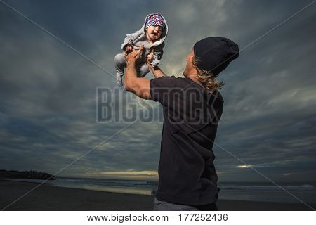 Father and little daughter play against sunset sky