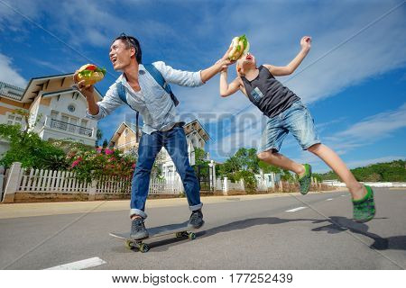 Man skating and try to eat hamburger and hungry boy jumping to bite a piece of a hamburger